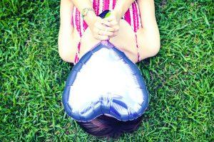 ハートの風船をもつ女性